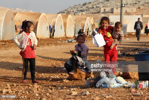A girl shows a notebook while she carries an infant as she laughs with other girls at the Furat camp for the displaced from Deir Ezzor north of the...