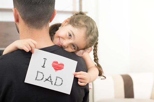 girl shows love dad card on her dad's shoulder 1152924900