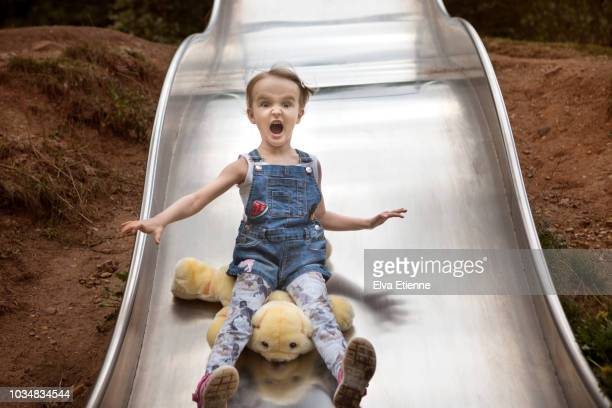 Girl (4-5) shrieking as she speeds down a wavy slide with soft toy
