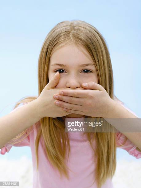 Girl (10-11) covering mouth, close-up, portrait