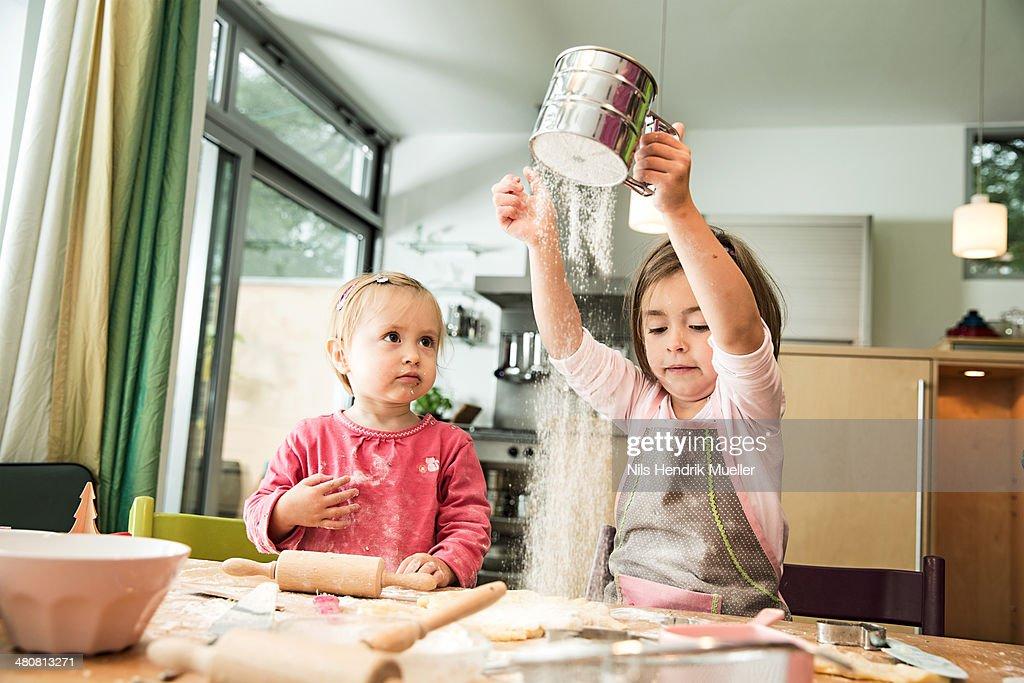Girl sieving flour in kitchen : Stock Photo