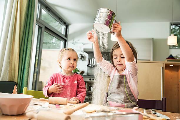 girl sieving flour in kitchen - 焗 預備食物 個照片及圖片檔