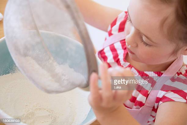 Girl sifting flour in kitchen