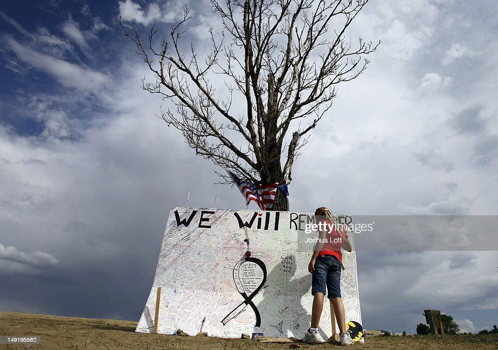 A girl signs a message board at a memorial across the street from the Century 16 movie theatre July 24, 2012 in Aurora, Colorado. The memorial was created for the victims that were killed during a mass shooting at the movie theater last Friday. Twenty-four-year-old James Holmes is suspected of killing 12 and injuring 58 others during a shooting rampage at a screening of 'The Dark Knight Rises.'