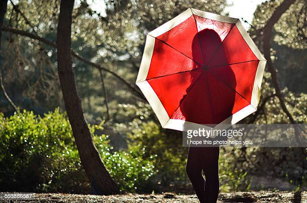 Girl silhouette behind red umbrella