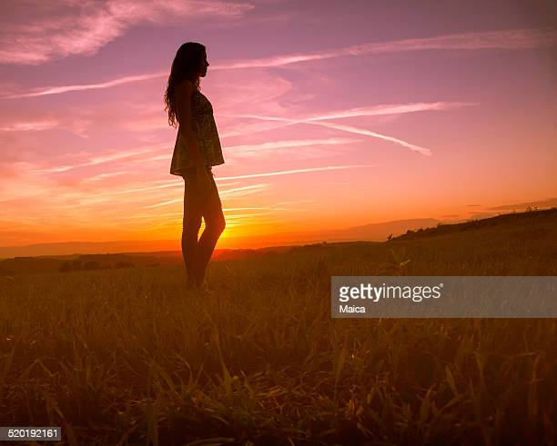 Girl silhouette in a sunset beautiful landscape