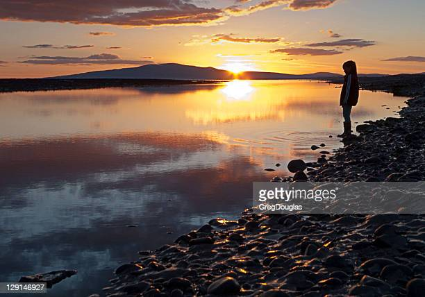 Girl silhouetted on shore with sunset reflections