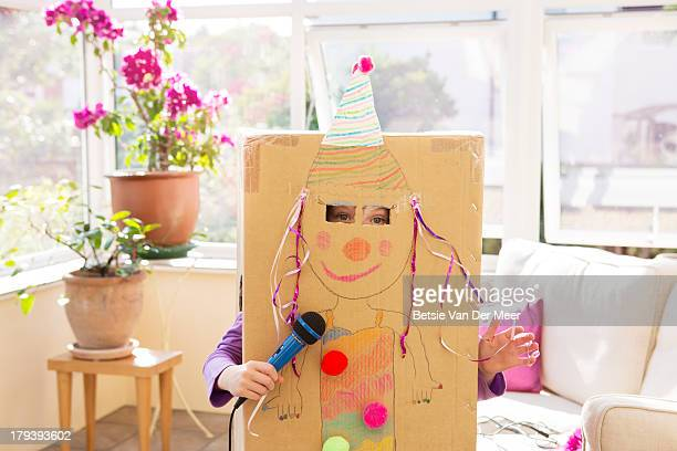 Girl singing hiding in decorated box