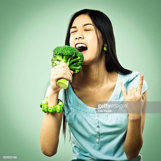 Mädchen singen in einem Brokkoli Mikrofon