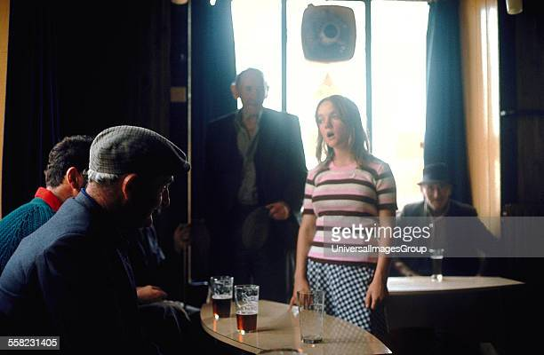 Girl singing in a pub with an audience of old men Puck Fair Killorglin Ireland 1973