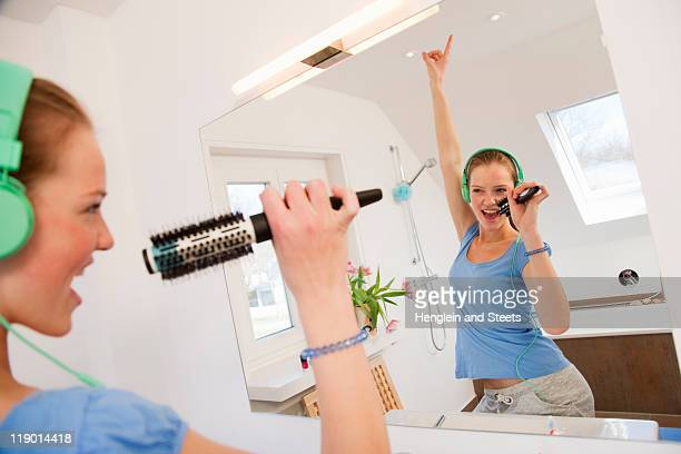 girl singing in bathroom - girl in mirror stock-fotos und bilder