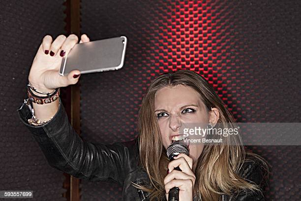 Girl singing into a microphone by making a selfie
