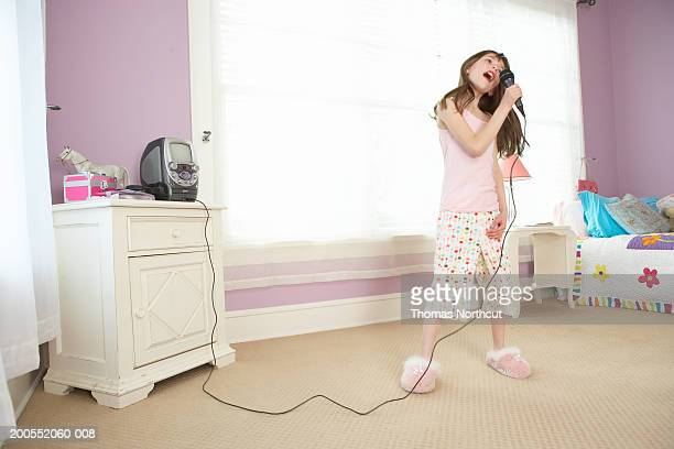 Girl (8-10) singing into microphone in bedroom