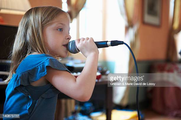 girl singing into microphone - saint ferme stock photos and pictures