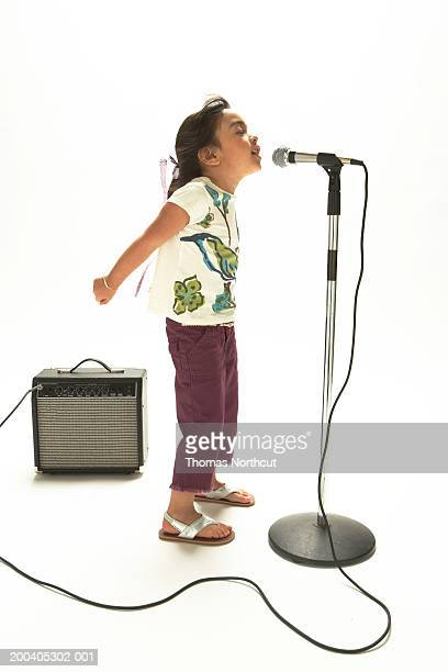 Girl (4-6) singing into microphone, side view