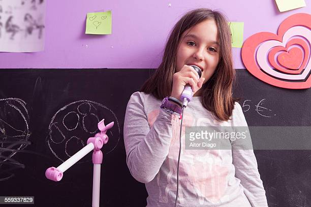 girl singing with a microphone  in her room. - cuerdas vocales fotografías e imágenes de stock