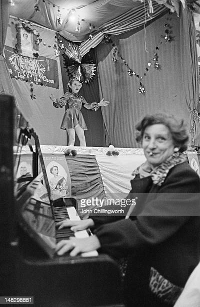 A girl sings on stage accompanied by a pianist at a party to celebrate the coronation of Queen Elizabeth II held in Morpeth Street in London's East...