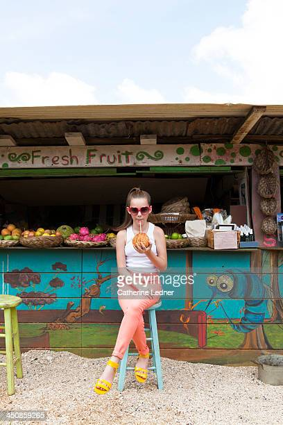 Girl sipping coconut at fruit stand