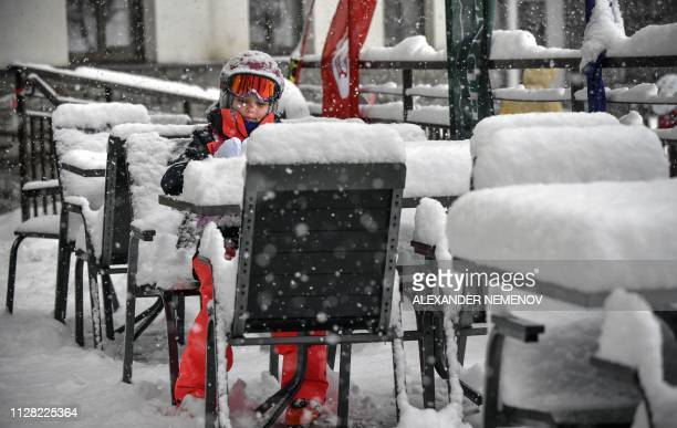 Girl sits at a table in a street cafe during heavy snowfall in the Rosa Khutor resort, outside Sochi, on March 1, 2019. - Organisers on March 1, 2019...
