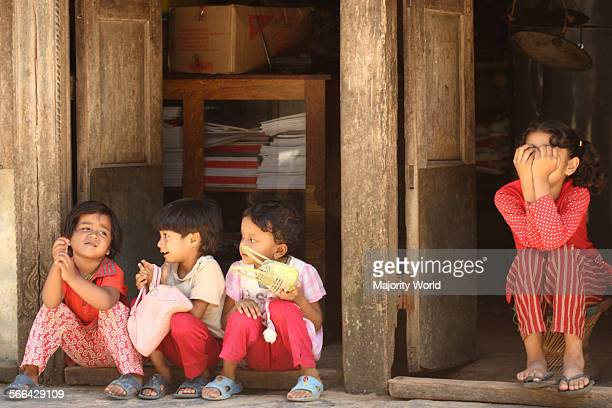 A girl sits at the entrance of her mother's shop keeping guard while her mother is away Three other children play at 'being mothers going shopping'...