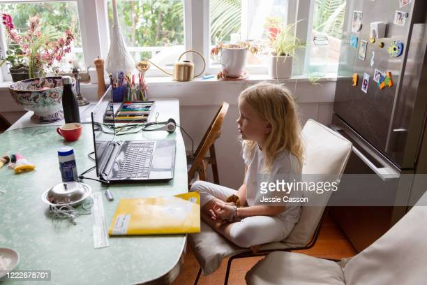 a girl sits at the kitchen table with her laptop during home schooling -  eラーニング ストックフォトと画像
