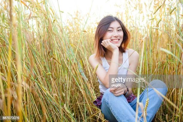 niña sentada en un campo entre las espigas de trigo