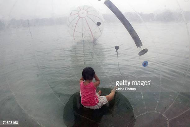 A girl sits in a water walking ball at Yuyuantan Park on August 10 2006 in Beijing China The ball that is 25 meters in diameter and filled with...