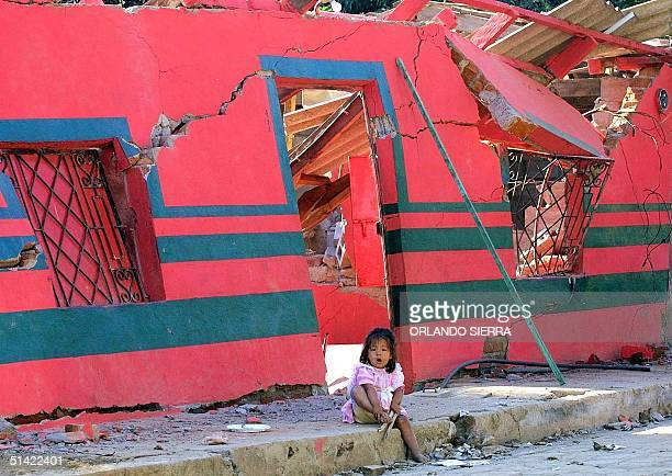 A girl sits in front of a building destroyed an earthquake 17 January 2001 in San Agustin El Salvador Authorities have reported 675 deaths but with...