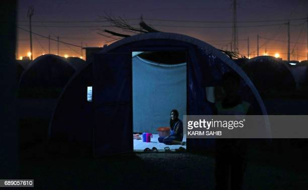 A girl sits inside a tent after sunset on the first fasting day of the Muslim holy month of Ramadan at alKhazir camp for the internally displaced...