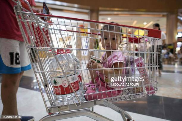A girl sits inside of a supermarket trolley after her dad bought water and food at a supermarket ahead of the arrival of the Super Typhoon Mangkhut...