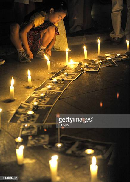 A girl sits next to the candles during a memorial event for the dead school children who were killed in the massive May 12 earthquake in Chengdu in...