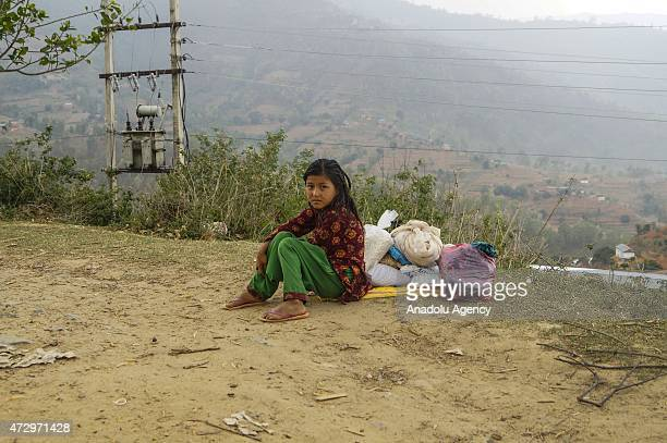 A girl sits next to the food supplies as she wait for her mother at Charuwa village some 52 Kilometer east from Kathmandu on May 11 2015 The number...