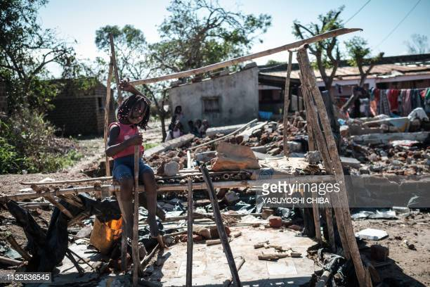 A girl sits on a kiosk destroyed by the cyclone Idai in Tica Mozambique on March 24 2019 Cyclone Idai smashed into Mozambique's coast unleashing...