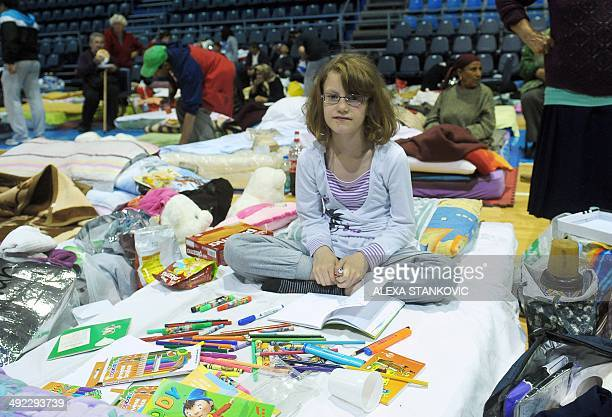 A girl sits on a matress with coloured felt pens and books in a collective centre for people evacuated from the flooded town of Obrenovac on May 19...