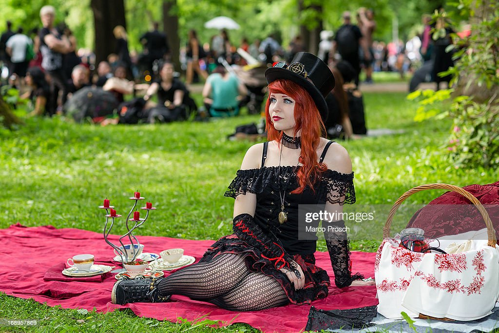 A girl sits on a red blanket on the lawn during the traditional park picnic on the first day of the annual Wave-Gotik Treffen, or Wave and Goth Festival, on May 17, 2013 in Leipzig, Germany. The four-day festival, in which elaborate fashion is a must, brings together over 20,000 Wave, Goth and steam punk enthusiasts from all over the world for concerts, readings, films, a Middle Ages market and workshops.