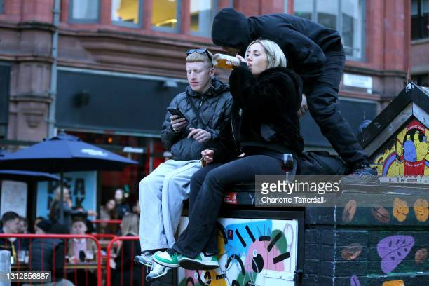 Girl sits on a wall drinking alcohol in Manchester's Northern Quarter on April 16, 2021 in Manchester, England. Pubs and Restaurants are expecting...
