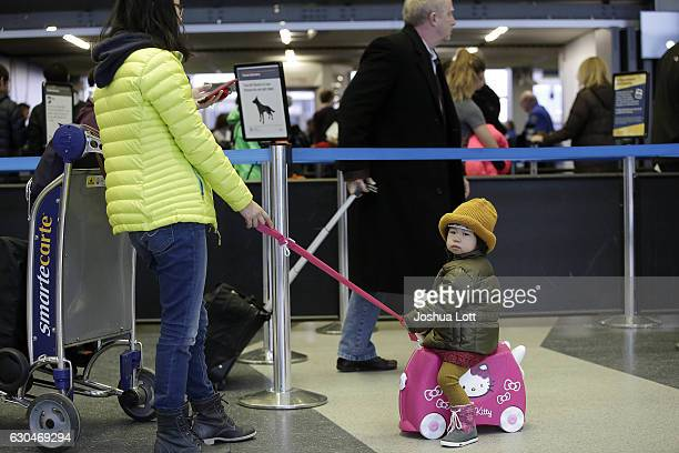 A girl sits on her toy as travelers walk though the TSA security line at O'Hare International Airport on December 23 2016 in Chicago Illinois O'hare...