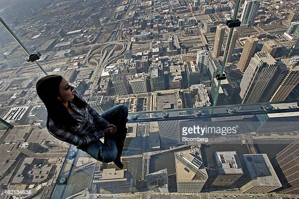 A girl sits on the glass balcony at the skydeck of the Willis Tower in Chicago Illinois US on Wednesday Feb 13 2013 Willis Tower formerly named the...