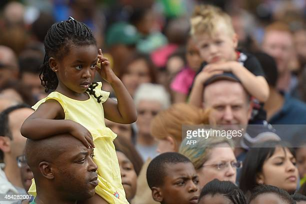 A girl sits on the shoulders of his father as people gathered outside South African former president Nelson Mandela home in Houghton Johannesburg on...