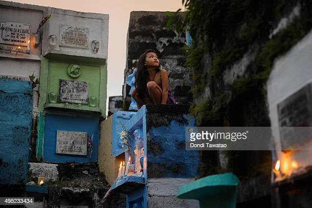 A girl sits on top of a tombstone at a public cemetery on November 1 2015 in Marikina City Philippines Millions of Filipinos flock to cemeteries...