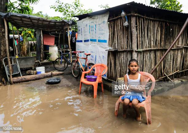 TOPSHOT A girl sits outside his flooded house by the overflowing of the river due to heavy rains in Tepalon Granada some 80 km east of Managua on...