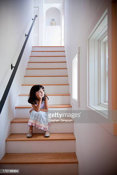 girl sits quietly in light-filled stairwell