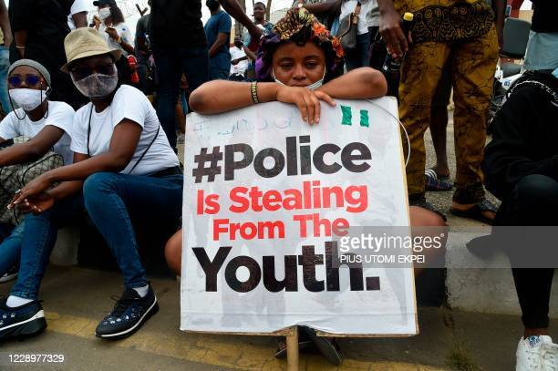 Girl sits while holding a placard in continuation of ongoing demonstrations to call for the scrapping of the controversial police unit at Ikeja, on...