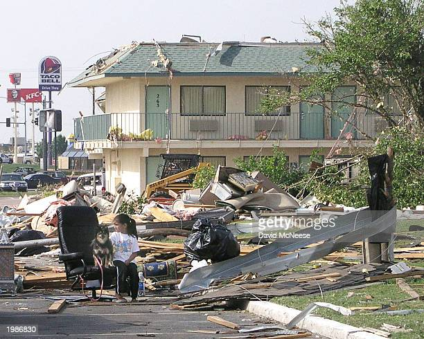 A girl sits with her dog at a motel damaged by a tornado along interstate 35 May 9 2003 in Moore Oklahoma A toranado destroyed 300 homes and injured...