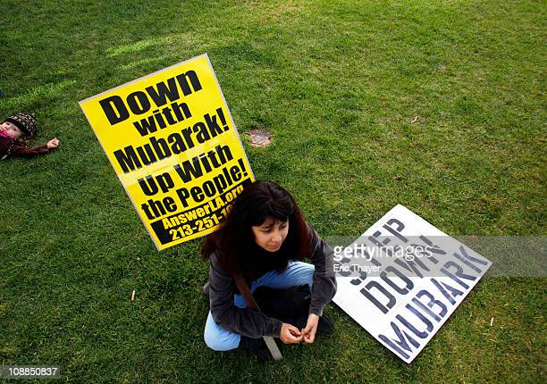 A girl sits with signs sits during a protest against the regime of Egyptian President Hosni Mubarak February 5 2011 in the Westwood neighborhood of...