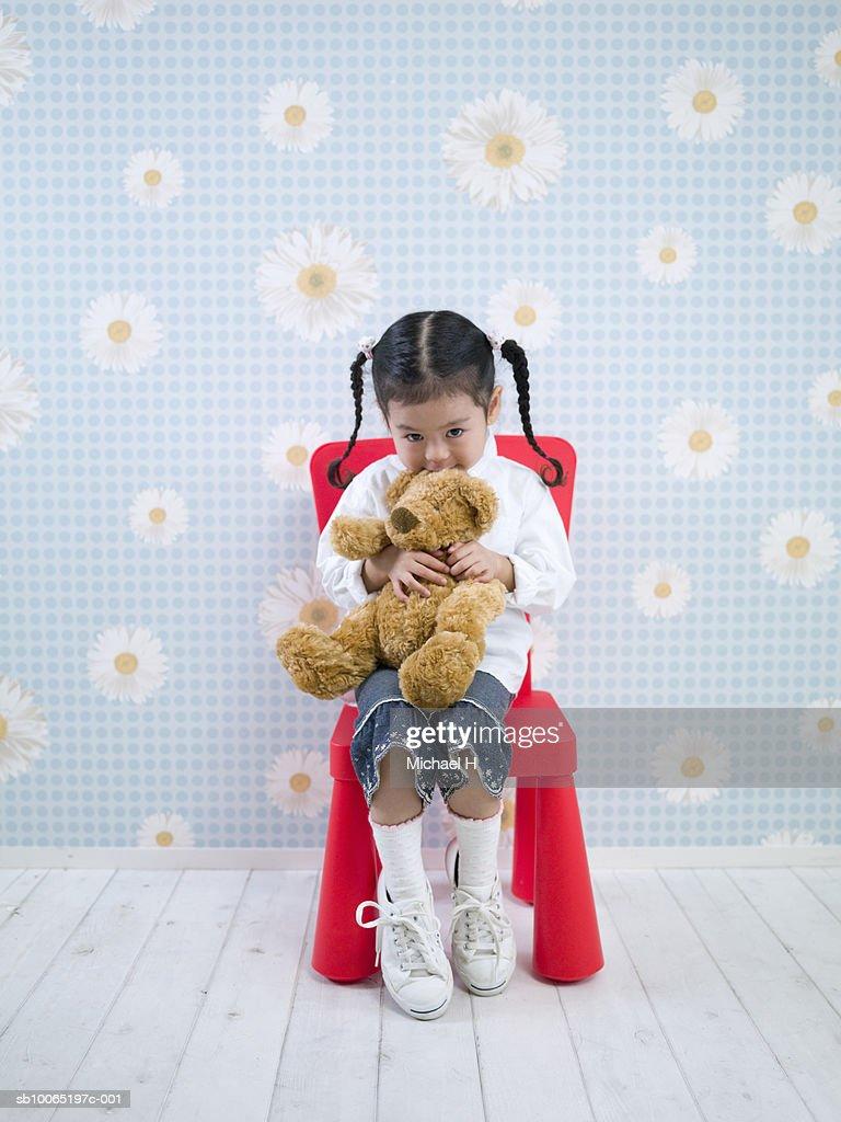 Girl Sitting Against Floral Wallpaper Holding Teddy Bear Portrait