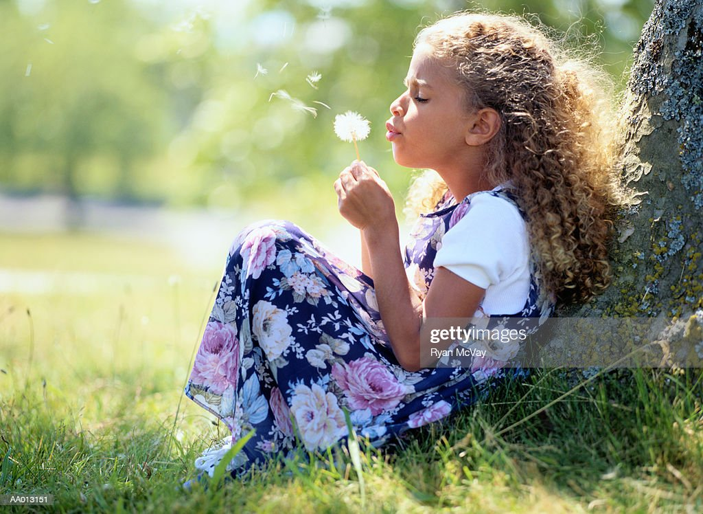 Girl (5-7) sitting against tree, blowing dandelion, profile : Stock Photo