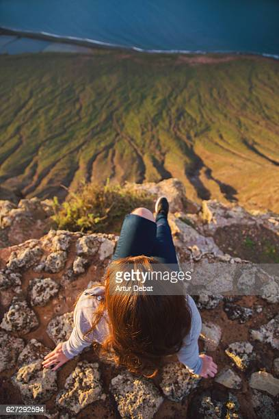 Girl sitting and contemplating the volcanic island of Lanzarote with nice sunset light from top of viewpoint during a travel vacations through the island.