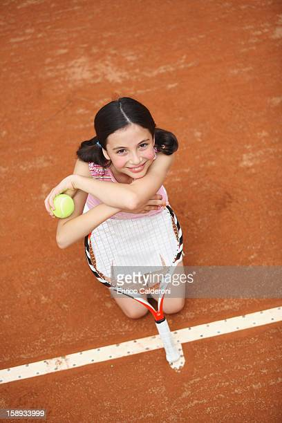 Girl Sitting And Looking Up In Clay Court