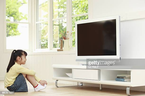 A girl sitting and watching TV.
